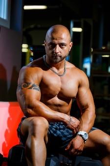 Sterke, volwassen, fitte, gespierde mannelijke trainer poseren voor een fotoshoot in de sportschool in sportkleding, pronken met zijn spieren