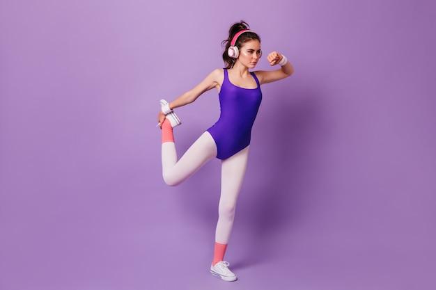 Sterke vrouw atleet doet oefeningen op muziek