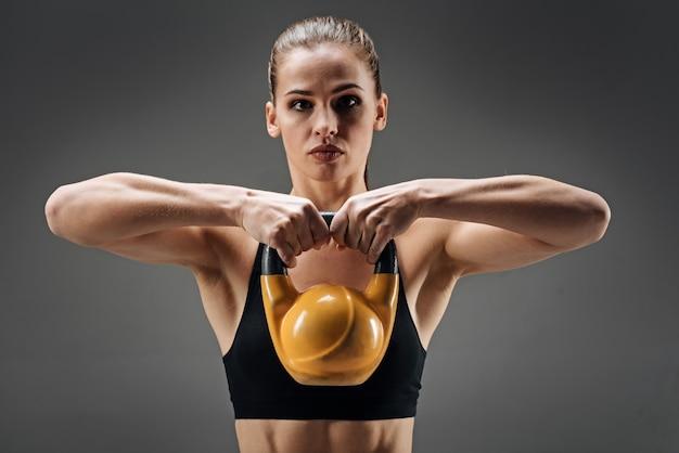 Sterke vrouw die gymnastiekgewicht aantoont