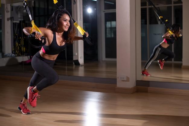 Sterke vrouw die trxoefening met riemen in de fitness gymnastiek doet