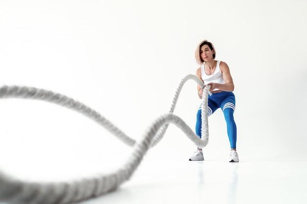 Sterke vrouw die werkt met zware touwen. foto van sportief die meisje in sportkleding op witte muur wordt geïsoleerd. kracht en motivatie.