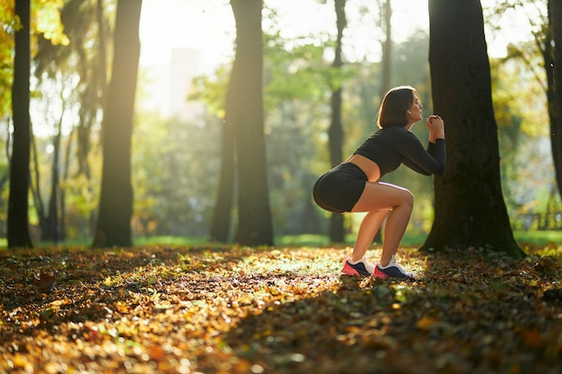 Sterke vrouw doet diepe squats in stadspark
