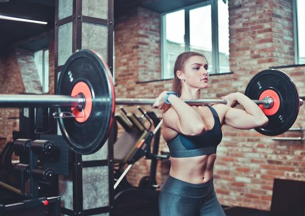 Sterke vrouw met sportkleding houdt barbell, meisje tillen met grote gewichten op sportschool
