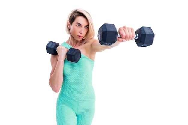 Sterke vrouw ponsen met halters in handen tijdens boksles