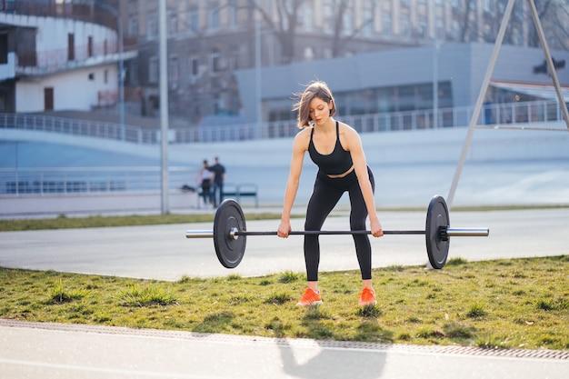 Sterke vrouw trainen met barbell sport fitness concept