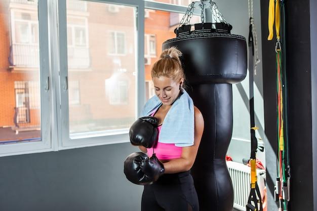 Sterke vrouwelijke bokser trekt bokshandschoenen aan
