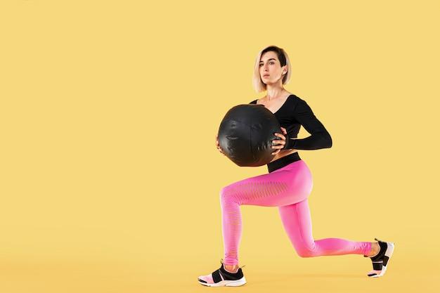 Sterke vrouwentraining met med bal. foto van sportieve latijnse vrouw in modieuze sportkleding op gele muur. kracht en motivatie.