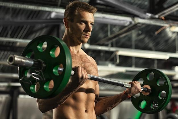 Sterke zelfverzekerde knappe man op zoek gericht tijdens het trainen met een halter in de sportschool