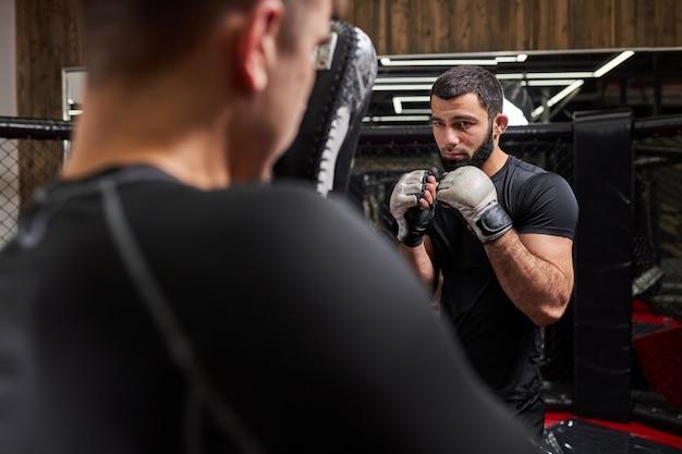 Sterke zelfverzekerde vechter of worstelaar die traint met professionele mma-vechter in sportschool in ring, samen voorbereiden op competitie. achteraanzicht op de mens