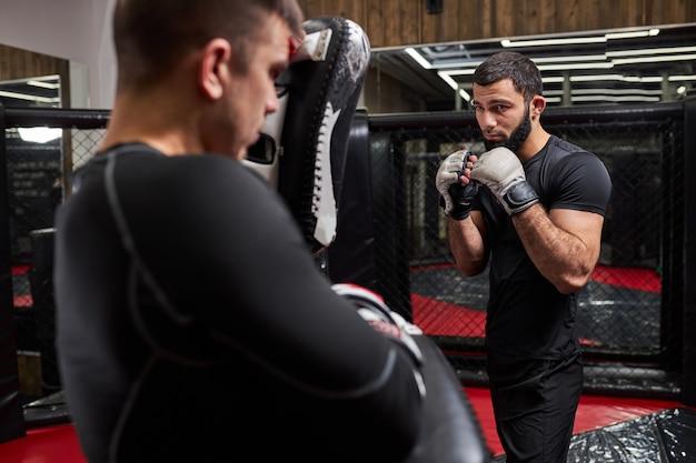 Sterke zelfverzekerde vechter of worstelaar die traint met professionele mma-vechter in sportschool in ring, samen voorbereiden op competitie