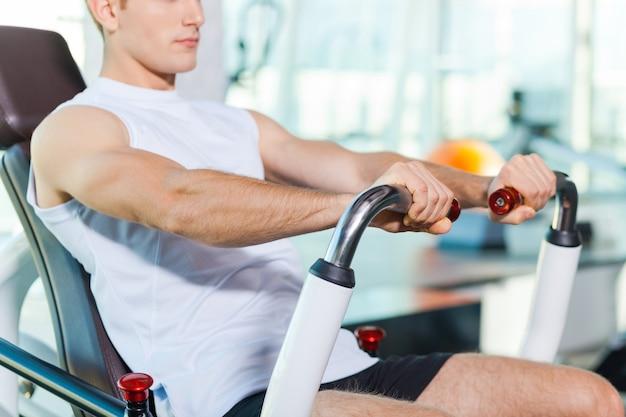 Sterkte en kracht. bijgesneden afbeelding van jonge gespierde man die aan het trainen is in de sportschool
