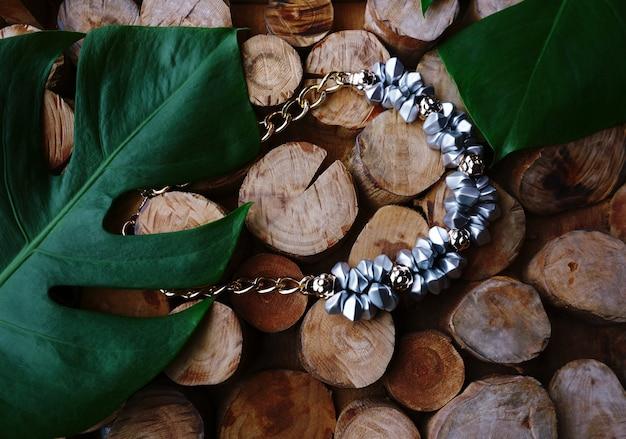 Sterling zilveren sieraden ketting op hout en groen blad achtergrond.