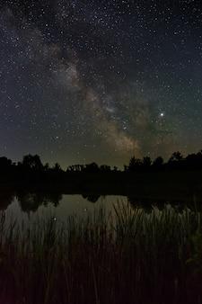 Sterren aan de hemel 's nachts. heldere melkweg over het meer.