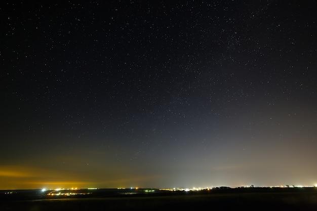 Sterren aan de nachtelijke hemel boven een stad met straatverlichting.