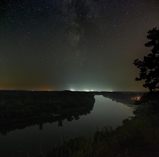 Sterren van de melkweg in de nachtelijke hemel boven de rivier.
