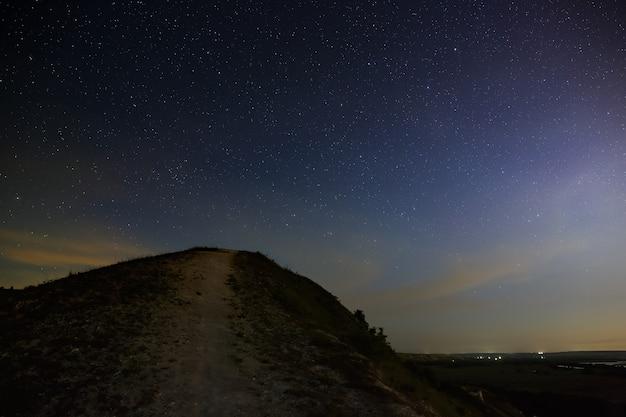 Sterren van de ruimte aan de nachtelijke hemel boven de riviervallei. landschap in de schemering bij lange blootstelling.