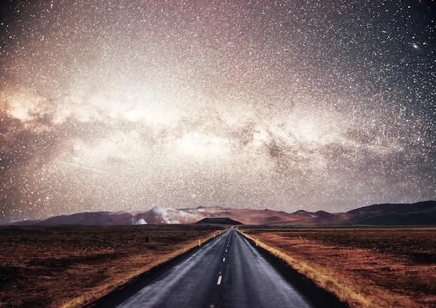 Sterrenhemel boven de bergen. de asfaltweg met witte aftekeningen.