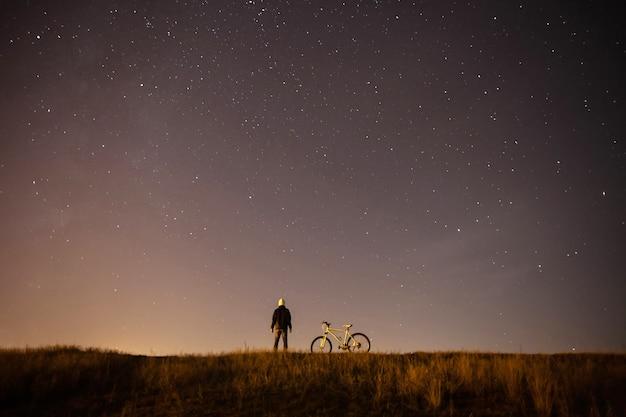 Sterrenhemel, nacht, astrofotografie, het silhouet van een man, een man die naast een mountainbike staat op een van een sterrenhemel, de witte fiets