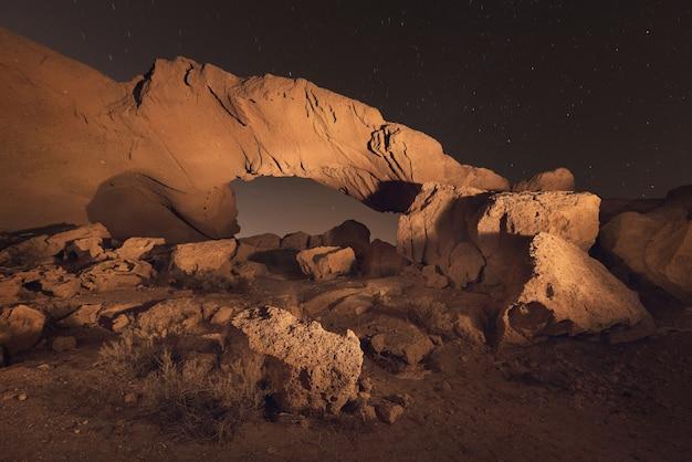 Sterrennachtlandschap van een vulkanische rotsboog in tenerife, canarische eilanden, spanje.