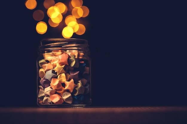 Sterrenorigami in glaskruik met een festivallicht, symbool voor giftviering