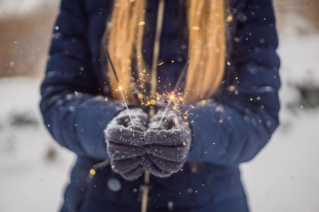 Sterretjes in vrouwelijke handen op een achtergrond van sneeuwval. kerstmis en nieuwjaar