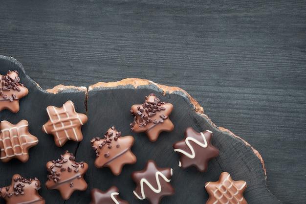 Stervormige chocolaatjes op donkere gestructureerde achtergrond, kopie-ruimte