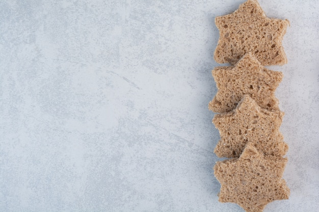Stervormige zwarte sneetjes brood op stenen oppervlak