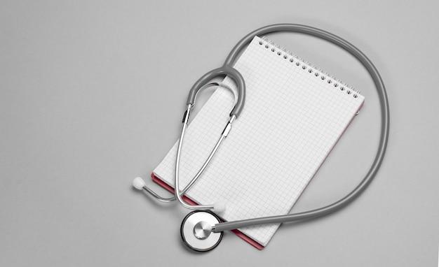 Stethoscoop, blocnote op een grijze achtergrond. gezondheidszorg en medisch concept met kopie ruimte. banner