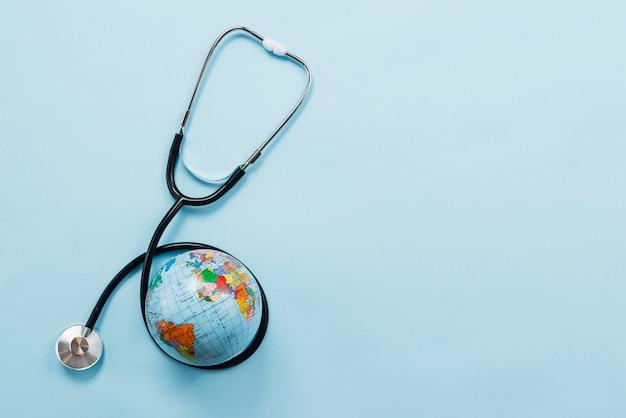Stethoscoop die aarde op blauwe achtergrond koestert