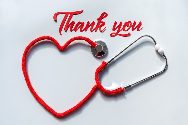 Stethoscoop die hart met zijn koord op witte achtergrond vormt. papierkunst van dank u belettering. gezondheidszorg concept. ruimte voor tekst. zachte focus. bovenaanzicht. plat leggen.