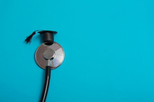 Stethoscoop en afgestudeerde hoed, op een blauwe achtergrond, bovenaanzicht, medische achtergrond afgestudeerde prestatie, background