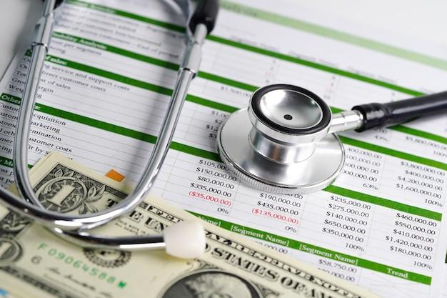 Stethoscoop en amerikaanse dollarbankbiljetten op spreadsheetpapier.