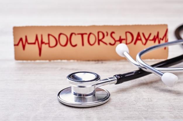 Stethoscoop en begroeting voor arts. papieren kaart op houten achtergrond. gefeliciteerd cardioloog.