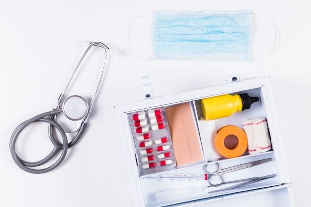 Stethoscoop en chirurgisch masker met eerste hulpuitrusting op witte achtergrond