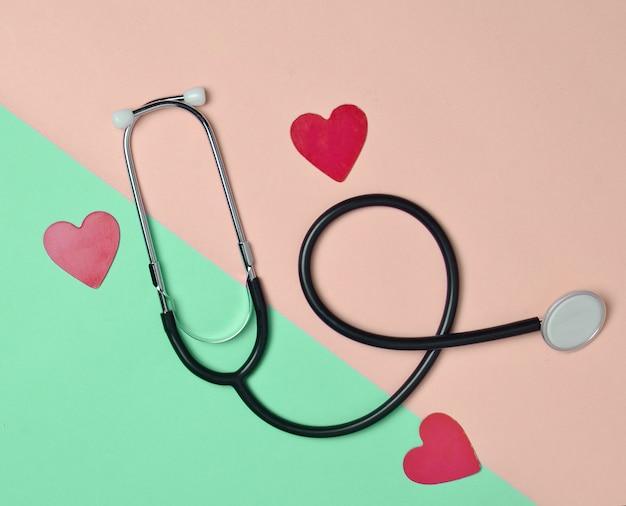 Stethoscoop en decoratieve harten op een gekleurde pastel