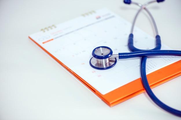 Stethoscoop en een kalender. aanstelling van de arts en dienst in het ziekenhuis.