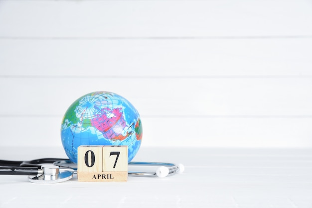 Stethoscoop en globe met 7 april tekst houten blok kalender op witte houten achtergrond.