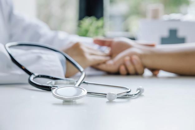 Stethoscoop en hand van arts geruststellende mannelijke patiënt