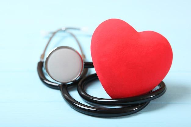 Stethoscoop en hart op houten achtergrondgezondheidsgeneeskunde