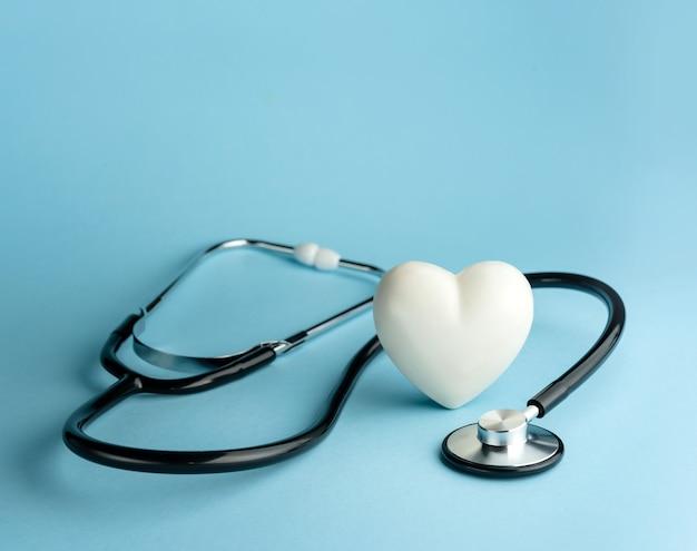 Stethoscoop en hartvorm op een blauwe achtergrond met kopieerruimte