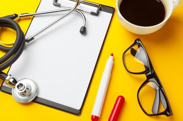 Stethoscoop en leeg klembord met glazen en marker