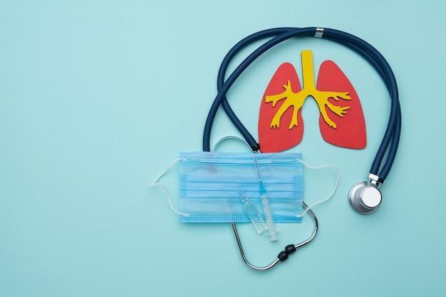 Stethoscoop en longen op een blauwe achtergrond met een masker, ampul en spuit.