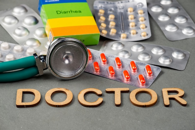 Stethoscoop en medicijnblisterverpakking op een leistenen vloer