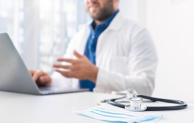 Stethoscoop en medisch masker op het artsenbureau op de achtergrond. arts voert een online patiëntenraadpleging uit met behulp van de computer