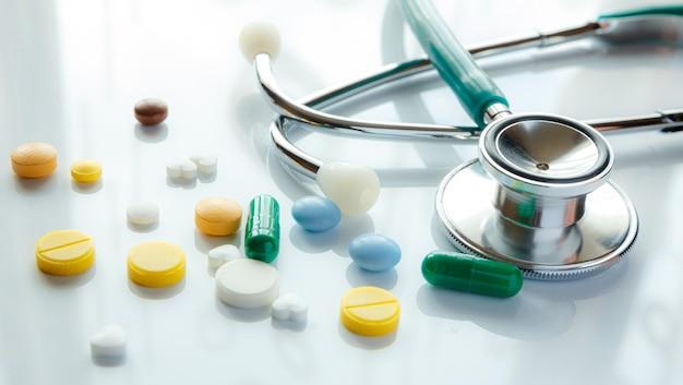 Stethoscoop en multi gekleurde pillen met reflectie