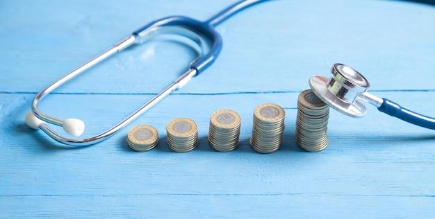 Stethoscoop en munten op de blauwe achtergrond.