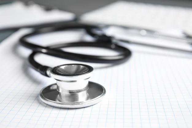 Stethoscoop en notitieboekje op tafel, close-up