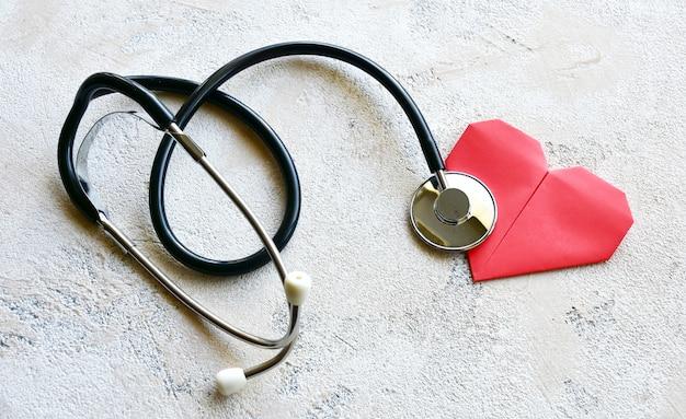 Stethoscoop en origamidocument rood hart op een steenachtergrond. bovenaanzicht.
