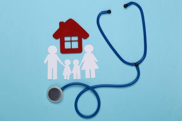 Stethoscoop en papieren ketting familie, huis op blauw, ziektekostenverzekering concept
