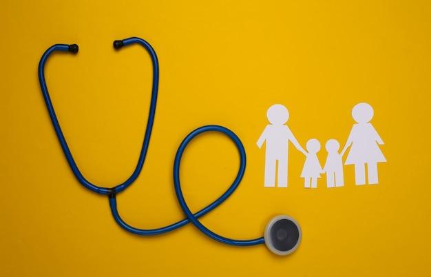 Stethoscoop en papieren kettingfamilie op geel, zorgverzekeringsconcept